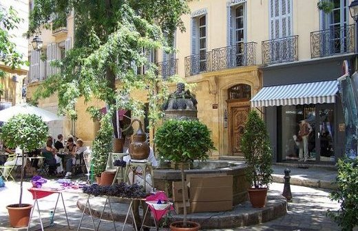 Fountain, café and market stall on a square in Aix en Provence